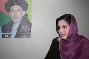 Lailuma Naimzai stands next to a photo of Afghanistan President Hamid Karzai in a Kabul precinct office of his campaign on Sunday. Dr. Naimzai heads up a local campaign office, overseeing a staff of 50.