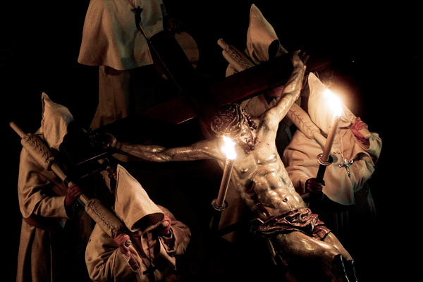 1 In Pictures Holy Week Penitents carry a figure of Christ on the cross